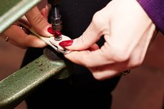 A woman uses a leather riveter to rivet a strip of leather used in the production of handbags / shoes stock photo