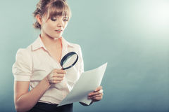 Woman uses magnifying glass to check contract. Business woman using magnifying glass to check contract instagram filter photo Royalty Free Stock Images