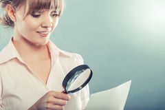 Woman uses magnifying glass to check contract Royalty Free Stock Photo