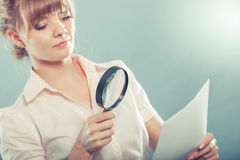 Woman uses magnifying glass to check contract Stock Photography
