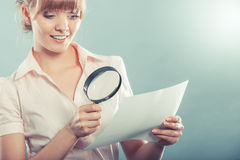 Woman uses magnifying glass to check contract Royalty Free Stock Photography