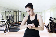 Woman uses smart watch at gym Royalty Free Stock Image