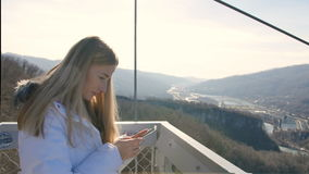 Woman uses smartphone with amazing view of the valley on the background. At sunny day stock footage