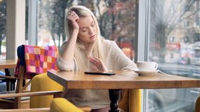 A woman uses a smartphone in a coffee shop and thinks. A young long haired woman is unhappy after using her smartphone in a cafe stock video