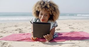Woman Uses A Tablet On The Beach stock video footage