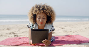 Woman Uses A Tablet On The Beach Stock Photography