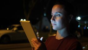 A woman uses a tablet in a city night. technology, communication and navigation.