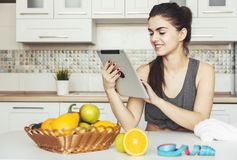 Woman Uses Tablet in Kitchen stock photos