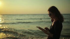 Woman uses tablet pc at the seaside stock video footage