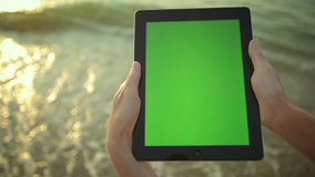 Woman uses tablet pc at the seaside greenscreen stock video