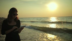 Woman uses tablet pc at the seaside stock footage