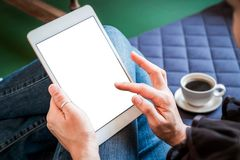 Woman uses tablet while relaxing at home with coffee on the sofa stock photos