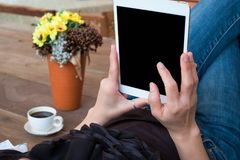 Woman uses tablet while relaxing at home with coffee on wooden f royalty free stock photos