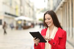 Woman uses a tablet in the street in winter. Happy woman uses a tablet in the street of an old town in winter royalty free stock photography
