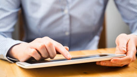 Woman Uses a Tablet on a Wooden Table Royalty Free Stock Photography