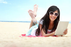 Woman uses touchpad tablet on the beach Stock Image