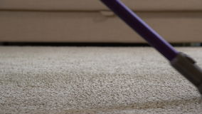 A woman uses a vacuum cleaner to clean the carpet. Close up stock footage