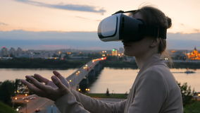 Woman uses virtual reality glasses in the city after sunset. Evening time, twilight. Relax, entertainment and technology concept stock footage