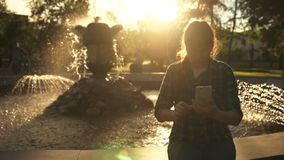 A woman uses a white smartphone near a fountain in the summer at sunset. A young woman in a plaid shirt send a text message using an application in a white stock footage