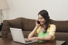 Free Woman Using A Laptop And Talking On Mobile Royalty Free Stock Image - 36255936