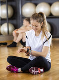 Woman Using Activity Tracker While Sitting In Gym Royalty Free Stock Photography