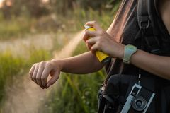 Woman using anti mosquito spray outdoors at hiking trip. Close-up of young female backpacker tourist applying bug spray on hands royalty free stock photos