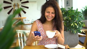 Woman using app on smartphone in cafe drinking coffee and laugh stock footage