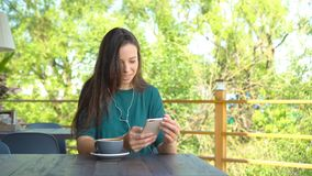 Woman with smartphone in cafe drinking coffee smiling and texting on mobile phone. Portrait of beautiful young girl stock video footage