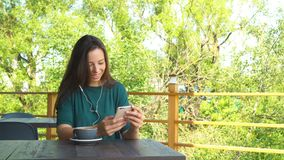 Woman with smartphone in cafe drinking coffee smiling and texting on mobile phone. Portrait of beautiful young girl stock footage
