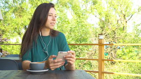 Woman using app on smartphone in cafe drinking coffee smiling and texting on mobile phone. Beautiful young female. Woman using app on smartphone in cafe drinking stock footage