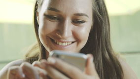 Woman using app on smartphone and smiling in cafe. stock footage