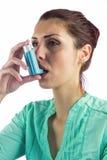 Woman using asthma inhaler Stock Photos