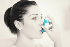 Woman using an asthma inhaler Royalty Free Stock Photography
