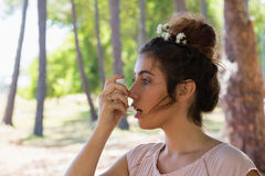 Woman using asthma inhaler in the park Stock Image