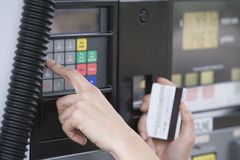 Woman Using ATM. Close-up of woman's hand using ATM machine at fuel station Royalty Free Stock Photos