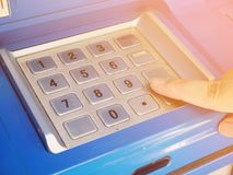 Woman using ATM machine to withdraw money. Woman press on ATM keyboard to entering PIN or pass code on ATM bank machine Royalty Free Stock Photo