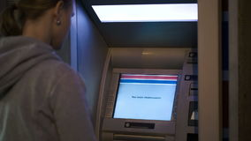 Woman using ATM outdoor in the evening Stock Photo