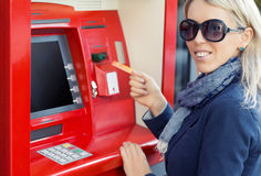 Woman using ATM to withdraw money. Happy woman using ATM to withdraw money Stock Photo