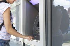 Woman using banking machine. Royalty Free Stock Image