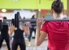 Woman using barbells. In bodypump class to gain muscles in the gym Stock Image