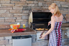 Woman using barbeque grill. Attractive blond Caucasian woman using a gas barbeque grill in an outdoor kitchen Stock Image