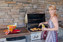 Woman using barbeque grill Royalty Free Stock Photos