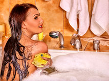 Woman using bath sponge in bathtub Stock Photography