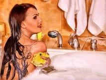 Woman using bath sponge in bathtub Stock Photography