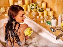 Woman using bath sponge in bathtub Royalty Free Stock Image