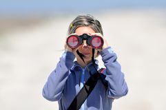 Woman using binoculars Royalty Free Stock Photography
