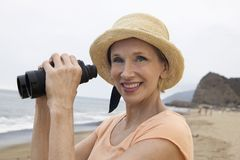 Woman using binoculars at beach (portrait) Royalty Free Stock Images