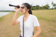 Woman using binoculars in the topical forest. Royalty Free Stock Images