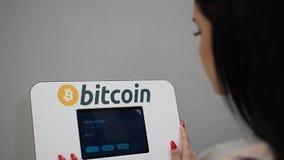 Woman using bitcoin ATM machine in HD VIDEO