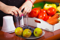 Woman using a blender to make a healthy juice at home Royalty Free Stock Images